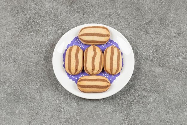 Délicieux biscuits à rayures au chocolat sur plaque blanche