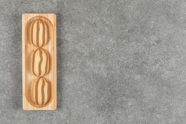 Délicieux biscuits à rayures au chocolat sur plaque en bois