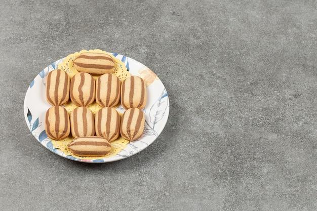 Délicieux biscuits à rayures au chocolat sur plaque colorée