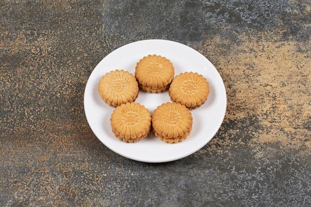 Délicieux biscuits remplis de crème sur une plaque blanche.