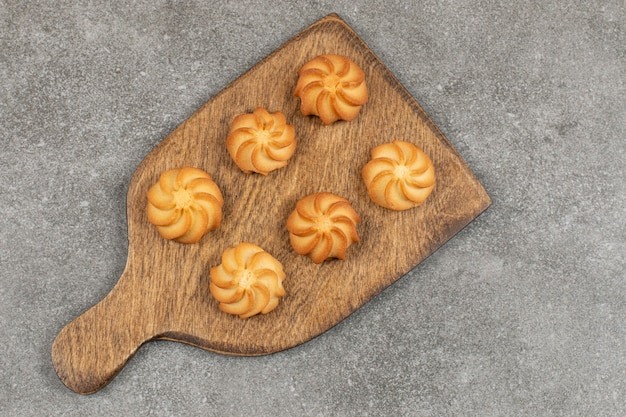 Délicieux biscuits sucrés sur planche de bois.