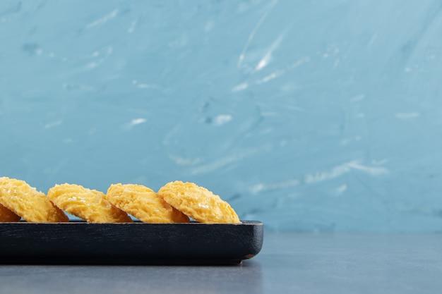 Délicieux biscuits sucrés sur plaque noire.