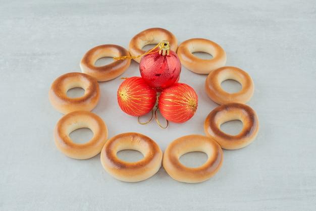 Délicieux biscuits sucrés ronds avec des boules de noël rouges sur fond blanc. photo de haute qualité