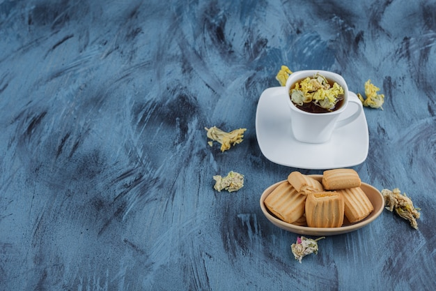 Délicieux biscuits avec tasse de tisane sur une surface bleue.