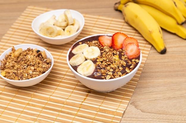 Délicieux bol aã§ai, sur table en bois, avec banane et fraise.