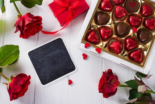 Délicieux bonbons au chocolat dans une boîte cadeau sur un fond en bois blanc