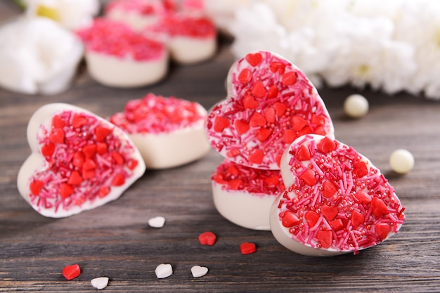 Délicieux bonbons au chocolat en forme de coeur sur table close-up