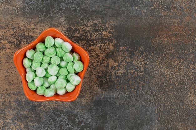 Délicieux bonbons au menthol vert dans un bol orange.