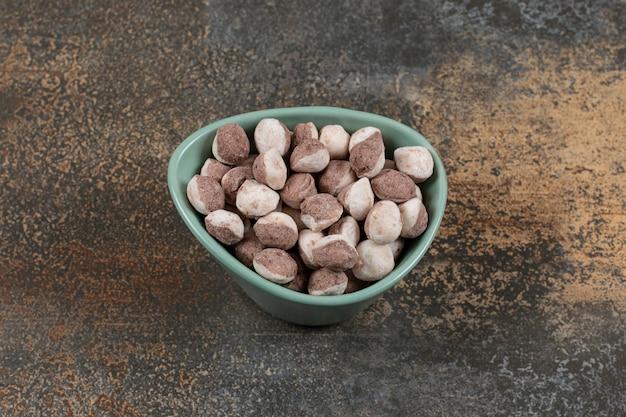 Délicieux bonbons bruns dans un bol bleu.