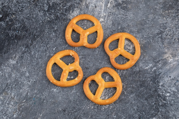 De délicieux bretzels secs salés placés sur une surface en marbre