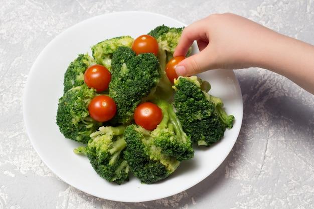 Délicieux brocoli et tomates cerises sur une plaque blanche sur une surface grise