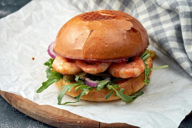 Délicieux burger aux crevettes, roquette, oignons et concombres marinés sur parchemin blanc. burger aux fruits de mer. l'alimentation de rue