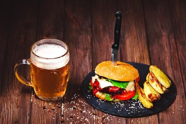 Un délicieux burger de bœuf avec de la laitue et des pommes de terre, un verre de bière servi sur une planche à découper en pierre. sombre
