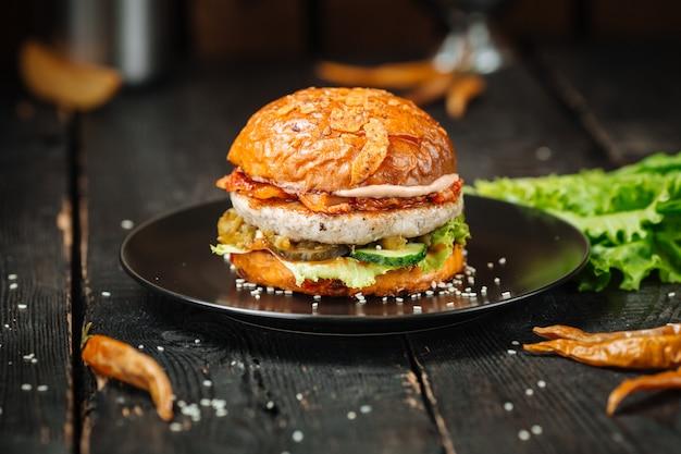 Délicieux burger avec une côtelette et de nombreuses couches savoureuses