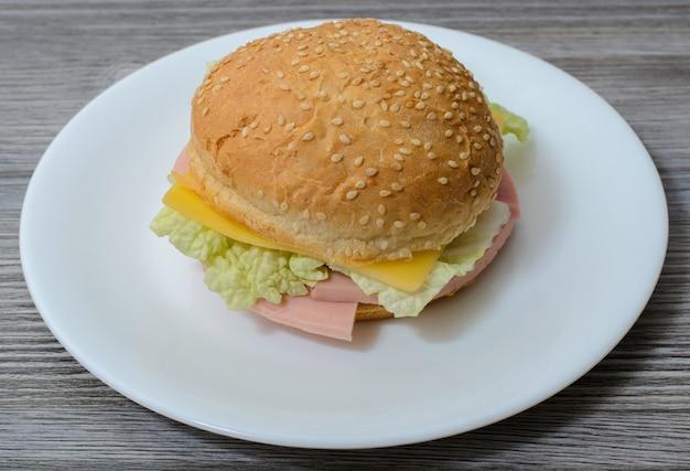 Délicieux burger délicieux avec du fromage et des saucisses sur une assiette blanche