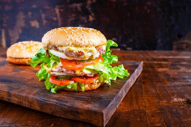 Délicieux burger fait maison avec de la laitue, du fromage, de l'oignon et des tomates sur une planche de bois rustique