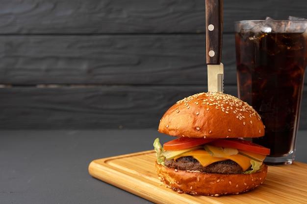 Délicieux burger sur fond en bois noir close up