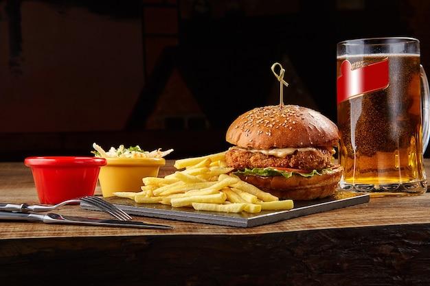 Délicieux burger frites avec sauce et verre de bière sur tableau noir