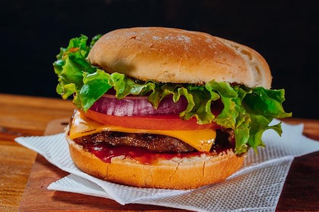 Délicieux burger avec laitue, tomate et oignon rouge et bacon sur du pain fait maison avec des graines et du ketchup sur une surface en bois et fond noir.