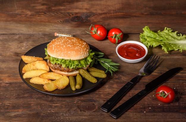 Délicieux burger maison grillé. délicieux hamburgers grillés. burger de boeuf artisanal et frites sur table en bois