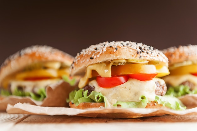Délicieux burger maison juteux. rouleau, bagel, avec une escalope juteuse de boeuf, sauces fromage feuilles de laitue fraîche
