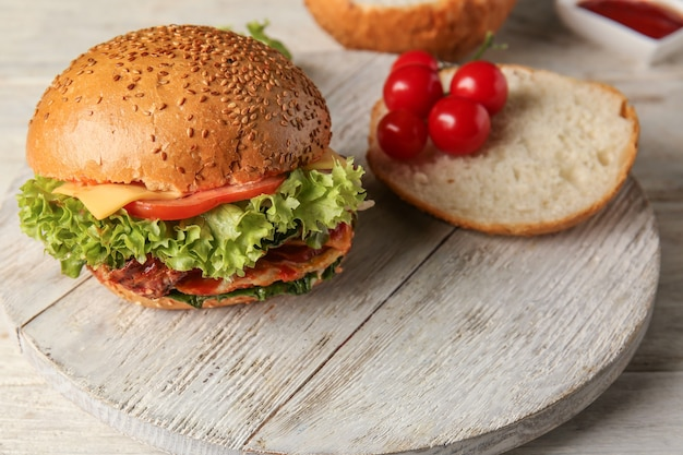 Délicieux burger, pain et tomate sur planche de bois