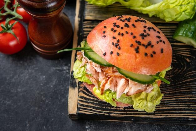 Délicieux burger de saumon avec pain rose sur fond noir