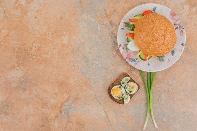 Délicieux burger avec des toasts aux œufs sur une table en marbre.