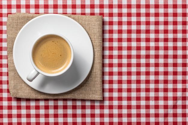 Délicieux café express, servi sur une nappe à carreaux vintage et une serviette en toile de jute.