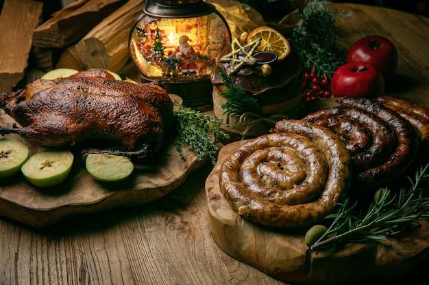 Délicieux canard de noël rôti aux pommes, saucisse maison et gâteau de noël