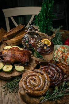 Délicieux canard de noël rôti aux pommes, saucisse maison, salade et gâteau de noël