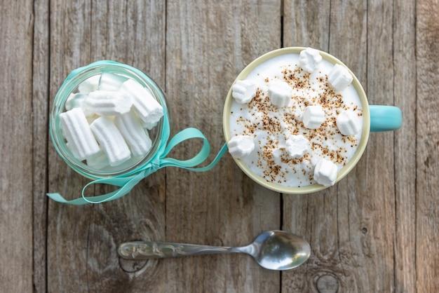 Délicieux cappuccino au caramel et aux guimauves dans une tasse bleu clair. vue de dessus.