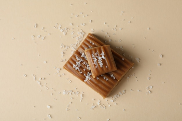 Délicieux caramel salé sur fond beige, vue du dessus