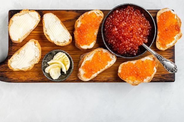 Délicieux caviar rouge dans un bol noir.