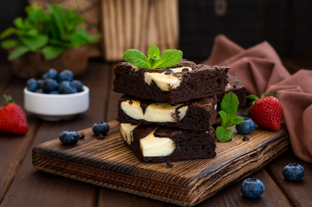 Délicieux cheesecake au brownie au chocolat avec des baies fraîches et de la menthe sur une planche de bois