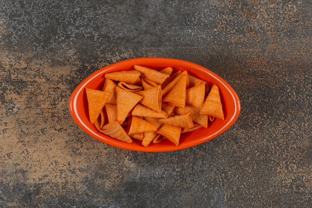 Délicieux chips triangulaires dans un bol orange.