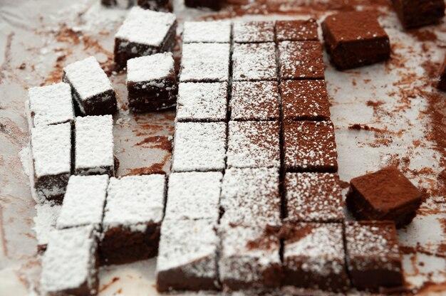 De délicieux chocolats crus faits maison coupés en formes carrées saupoudrées de sucre en poudre