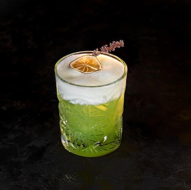 Délicieux cocktail d'alcool de kiwi vert et rhum avec blanc d'oeuf mousseux