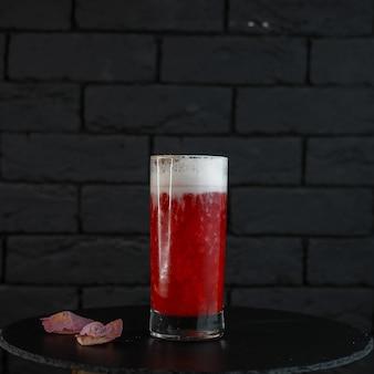 Un délicieux cocktail alcoolisé sucré dans un cristal dans un verre avec de la vodka et du rhum blanc avec l'ajout de jus de canneberge naturel se dresse sur une table décorée de pétales de roses roses.