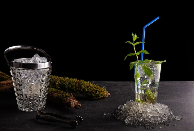 Délicieux cocktail à la menthe rafraîchissant appelé mojito avec rhum et citron vert, boisson froide ou boisson avec de la glace sur mur noir