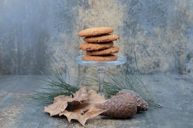 Délicieux cookies sur bocal en verre avec des feuilles et des pommes de pin sur fond de marbre.