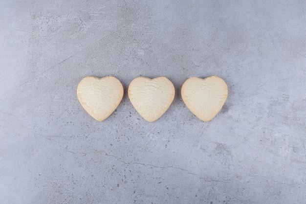 Délicieux cookies en forme de coeur placés sur une table en pierre.