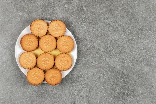Délicieux cookies remplis de crème sur plaque blanche
