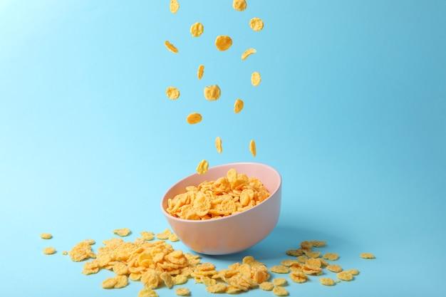De délicieux cornflakes tombant dans une assiette sur un fond coloré