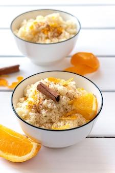 Délicieux couscous maison aux oranges et cannelle sur fond de bois rustique. nourriture végétalienne savoureuse.