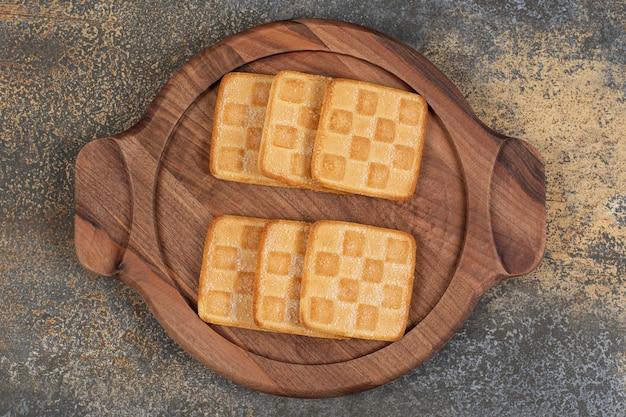 Délicieux craquelins sucrés sur planche de bois.