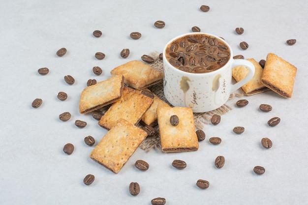 Délicieux craquelins sucrés avec une tasse de café blanc sur un sac. photo de haute qualité