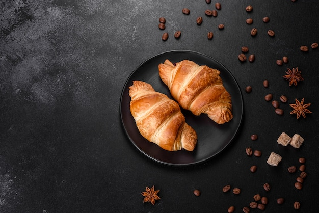 Délicieux croissant français croustillant frais avec des grains de café sur le tableau noir