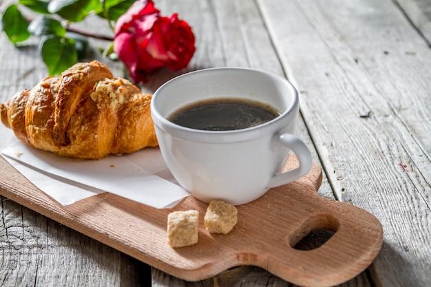 Délicieux croissants frais avec café et rose