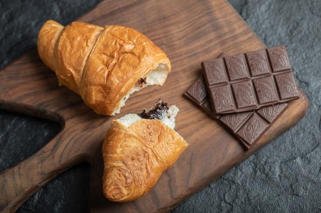 De délicieux croissants avec de savoureuses barres de chocolat sur une planche en bois.